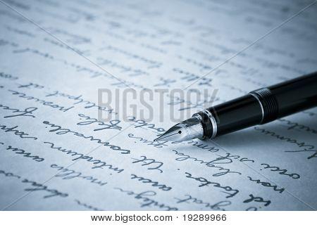 Imagem de ouro caneta-tinteiro na página escrita em tons azul. Foco nítido em bico de pena.