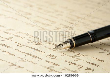 Caneta-tinteiro ouro na página escrita. Foco nítido em bico de pena.
