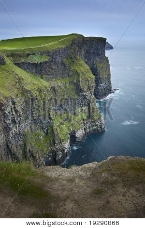 Cliffs of Moher at twilight. Vertical orientation view with pathway at bottom of frame.