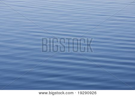Flawless blue water with soft ripples running diagonally through frame. Focus at center, with all texture smooth due to water texture.