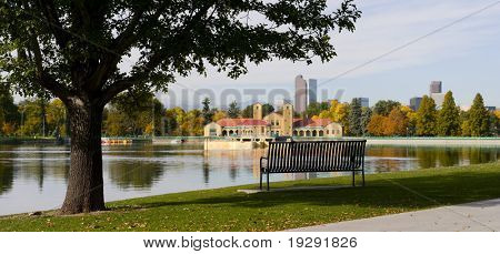 Denver city skyline with view of city park lake and bench. Critical focus on bench and silhouetted tree at left.