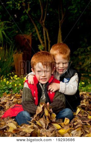 Two happy and smiling brothers sitting and hugging in pile of autumn leaves in garden