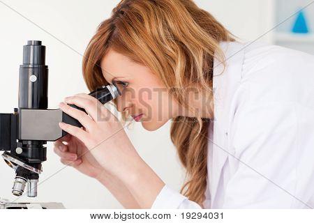 Attraktive blonde Wissenschaftler Blick durch ein Mikroskop