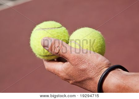 Tennis player holding two balls in his hand on court