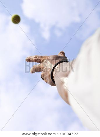 Tennis player trowing up a ball with his hand to serve blue sky
