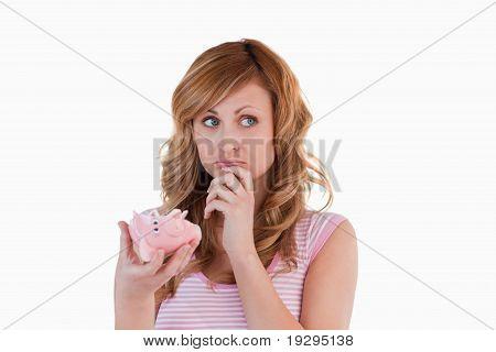 Woman perplexed concerning her broken piggybank