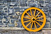 picture of stagecoach  - An old yellow wooden wagon wheel leaning against a stone wall - JPG