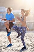 Strong lean couple doing intense high knees exercise on sand, keeping fit healthy lifestyle poster