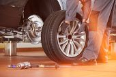 Low section of male mechanic repairing cars tire in repair shop poster