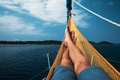 Man relaxes in a hammock set on a yacht poster