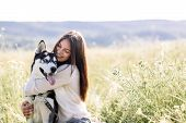Beautiful Girl Plays With A Dog (black And White Husky With Blue Eyes) Green Field poster