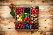 Mix of fresh berries with leaves in vintage wooden box on rustic wooden background. Top view. Raw he poster