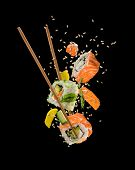 Sushi pieces placed between chopsticks, separated on black background. Popular sushi food. poster