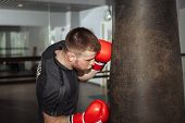 Постер, плакат: A Young Man Is Boxing In The Hall Attentive Sportsman In The Boxing Hall Practicing Boxing Punches
