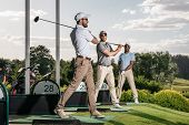 Group Of Golf Players Playing Golf Together At Golf Course poster