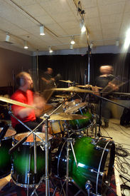 stock photo of recording studio  - A bass player guitar player and drummer recording tracks in a recording studio - JPG