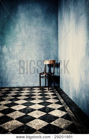 grunge room with blue old walls tiled floor and wooden chair in corner