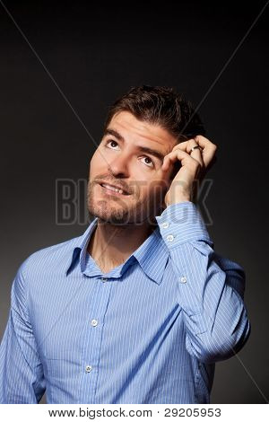 Closeup portrait of a casual young pensive businessman looking up at copyspace