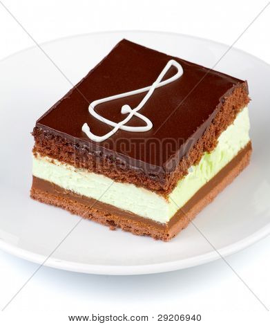 Chocolate cake with a treble clef sign made with cream. Isolated on white.