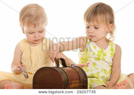 Two Little Blonde Girls Playing With A Wooden Chest