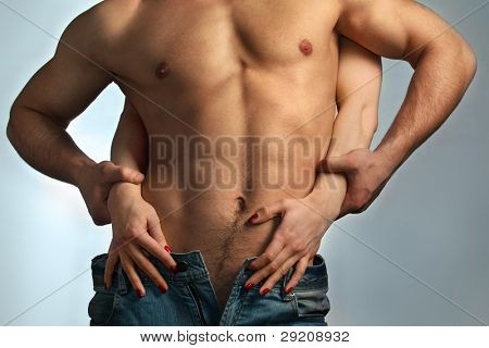 Sexy muscular naked man and female hands unbuckle his jeans