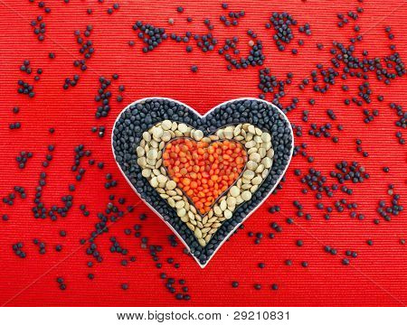 different types of grains of lentils in the form of heart , red cloth background