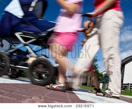 mother with small children and a pram crossing a street (motion blurred image)