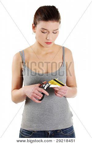 Traurige junge Frau hat ihre Kreditkarte vor einem weißen Hintergrund zu zerstören