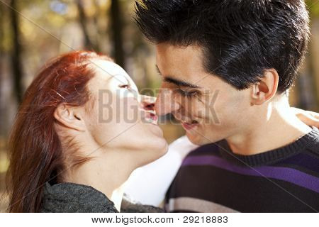 Love and affection between a young couple at the park (selective focus with shallow DOF)