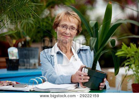 Retrato de uma mulher sênior que trabalha em um centro de jardim