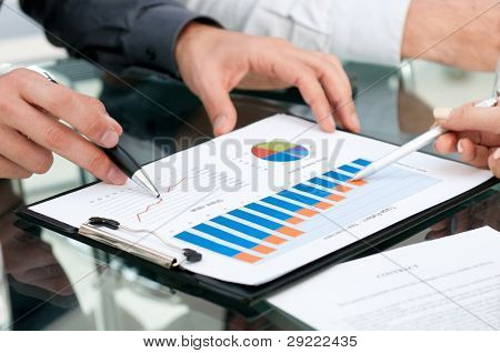 Closeup of business people analyzing growing charts during a meeting