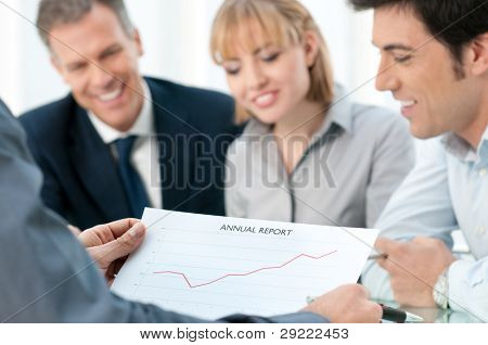 Business team analyzing together their positive annual report at meeting in office