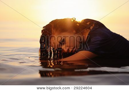 Woman In Water At Sunset