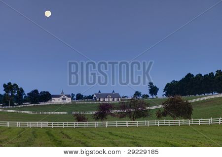 Moon rising over a horse farm
