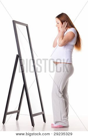 Pregnant Woman Stands Before Mirror.
