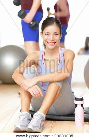 Fitness woman happy in gym smiling after training sitting taking a break on workout mat. Fit mixed race Chinese Asian / Caucasian female fitness model in gym.