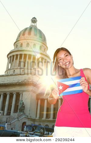 Havana, Cuba - Capitol and tourist with cuban flag in front of the National Capitol Building. Cuba travel concept photo with beautiful smiling happy woman tourist.