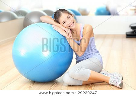 Fitness woman in gym resting on pilates ball / exercise ball after training. Beautiful multiracial fitness model in gym.