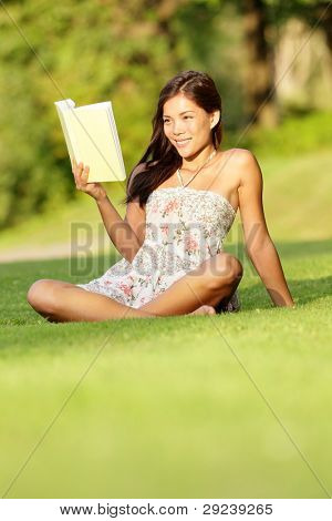 Woman reading book in spring / early summer. Cute student girl in sundress sitting in grass in park reading book smiling happy. Beautiful multiracial Asian / Caucasian female model.