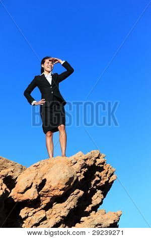 Business woman looking from mountain top. Business future concept image - businesswoman looking at horizon. Young multiracial executive.