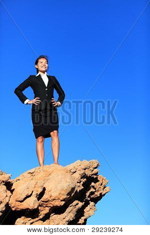 Success and challenges - business concept image. Successful business woman reaching goals overcoming challenges and adversity standing on mountain top in suit.