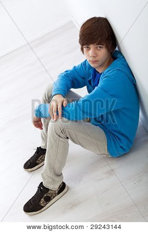 Sad teenager boy sitting on the floor leaning against the wall