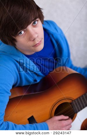 Portrait of teenager boy playing the guitar and dreaming away