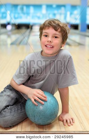 smiling happy boy sits on floor with blue ball in bowling club