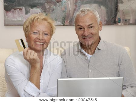 Portrait of a senior couple shopping using computer laptop.
