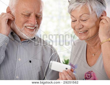 ¿Feliz pareja de ancianos con reproductor de mp3, escuchar música, sonriendo.?