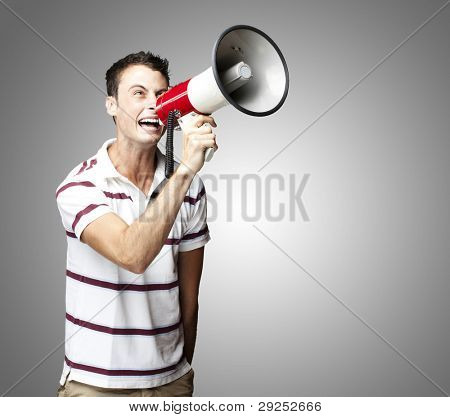 portrait of a young man shouting with a megaphone over a grey background