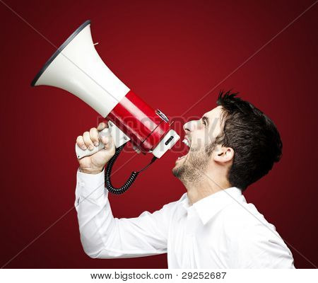 portrait of a handsome young man shouting using a megaphone over a red background
