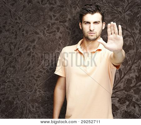 portrait of a handsome man doing a stop gesture against a vintage background