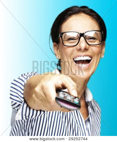 portrait of a middle aged woman laughing using a remote control against a blue background